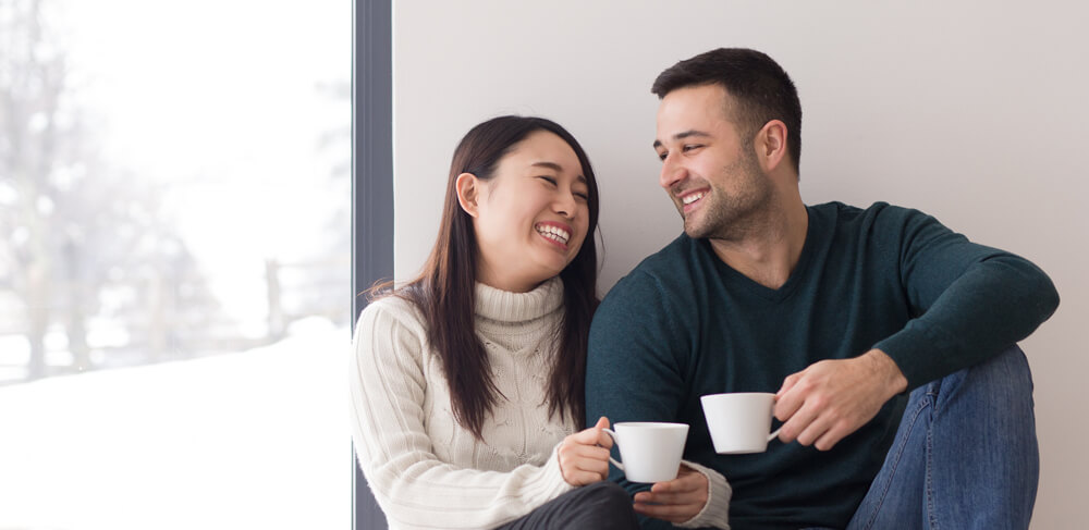 couple drinking coffee indoors on cold winter day