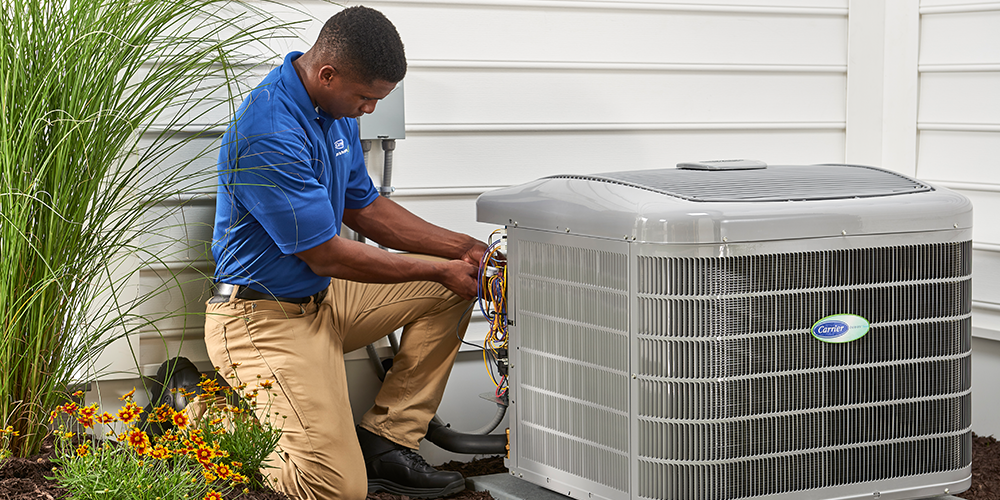 Technician services air conditioner outside as part of routine heating and cooling maintenance.